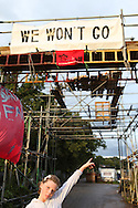 Irish Traveller girl showing the &quot;We won't go&quot; sign. Dale Farm in Essex, the UK largest Travellers' site. To support the Irish Travellers who own the land but never got planning permission and were about to be evicted by Basildon Council, some activists set up a Camp, called Camp Constant (after the name of the bailiffs' company, Constant &amp; Co). <br /> Irish Traveller grumpy boy outside his family's caravan in Dale Farm. The largest Traveller community in the UK, Dale Farm was under threat of bulldozing. Ninety families were facing the largest eviction of its kind in recent memory, a nightmare which forced its residents to camp again on roadsides and car-parks as the site was finally and violently evicted in October 2011.