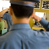 Prison warders salute each other in a workroom full of elderly prisoners,  in Onomichi prison , Japan. Monday, May 19th 2008. The inmates undertake 6 hours a day of light work.