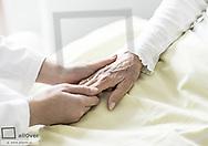 Pflegerin haelt die Hand einer Seniorin (model-released)