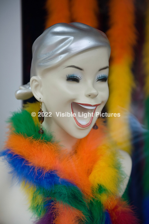 Laughing mannequin with a colorful boa in a store window.