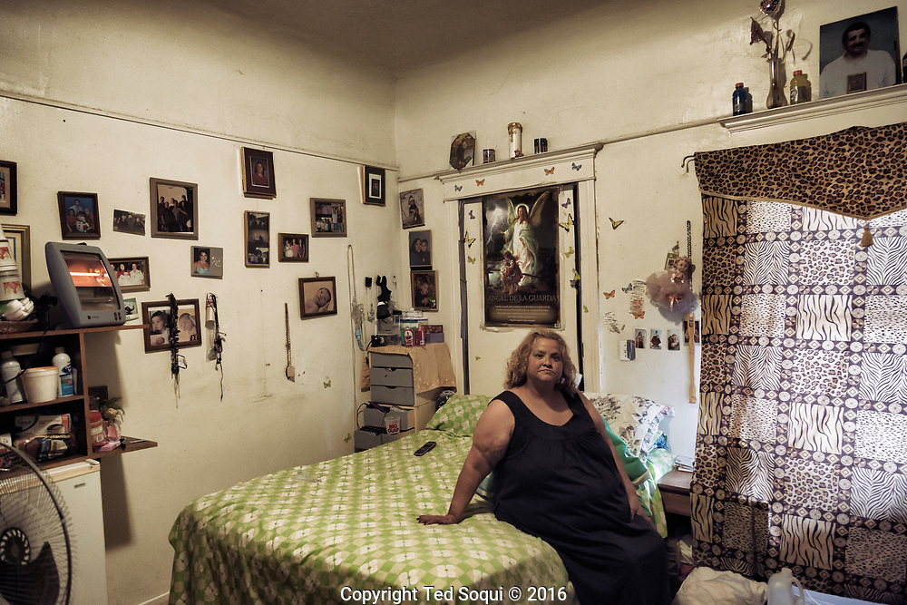 Isabelle Lopez inside her room, Santa Ana, CA.<br /> She was abandoned by her family and is now lives in a two bedroom home that rents rooms to over 10 people. Most of the walls in the home are made of paper to separate the renters, there is only one bathroom.<br /> She is also suffering from cancer and other illnesses.
