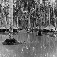Four Marines wade up the main street of their camp area on Guadalcanal, while a fifth (first tent on the left) bails out his foxhole.