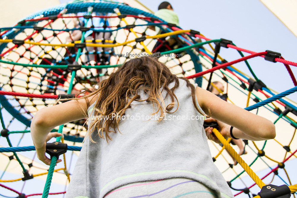 Young girl back to camera plays in the playground