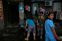 A picture made available on 30 July 2013 of Chinese residents doing their washing outside their home in a slum or shanty town area by the second ring road of Beijing, metres away from the prosperous Central Business District (CBD), separated only by a busy highway in China, 29 July 2013. Beijing announced plans to spend 500 billion yuan (61.5 billion euros) to renovate shanty towns within the fourth ring road according to local media. The five-year plan is expected to affect more than 230,000 households. China's massive urbanization push has resulted in the creation of large pockets of shanty towns and slums in urban areas as millions of migrant workers shifting to the cities are often priced out of city-centre properties. Slum or shanty town dwellers often live in dirty and cramped conditions, where they have no running water in their homes and have to share toilet and shower facilities.
