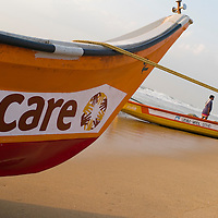 A Care donated boat on the beach of Santhome. Santhome Beach and adjoining Marina Beach in Chennai, India were hit hard by the 2004 Tsunami. Fishermen and their families were the main victims living in their lightweight huts on the long and flat beaches of the area. All structures within 300 metres of the sea have now been banned and any left standing after the Tsunami were demolished. The fishermen and their families have now been relocated to government blocks of flats which has become a Santhome slum for fishermen and their families.