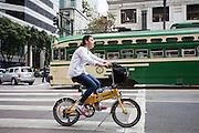 Een vrouw fietst op een vouwfiets in San Francisco. De Amerikaanse stad San Francisco aan de westkust is een van de grootste steden in Amerika en kenmerkt zich door de steile heuvels in de stad. Ondanks de heuvels wordt er steeds meer gefietst in de stad. <br /> <br /> Cyclists in San Francisco. The US city of San Francisco on the west coast is one of the largest cities in America and is characterized by the steep hills in the city. Despite the hills more and more people cycle