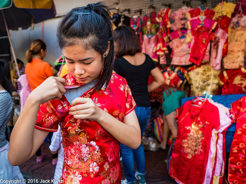 "31 JANUARY 2016 - BANGKOK, THAILAND: A woman tries on a traditional dress while she shops for new clothes at a stand on Yaowarat Road, in Bangkok's Chinatown district, before the celebration of the Lunar New Year. Chinese New Year, also called Lunar New Year or Tet (in Vietnamese communities) starts Monday February 8. The coming year will be the ""Year of the Monkey."" Thailand has the largest overseas Chinese population in the world; about 14 percent of Thais are of Chinese ancestry and some Chinese holidays, especially Chinese New Year, are widely celebrated in Thailand.             PHOTO BY JACK KURTZ"