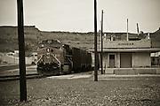 USA, Arlizona, Kingman. A freight train passes through an abandoned train station.