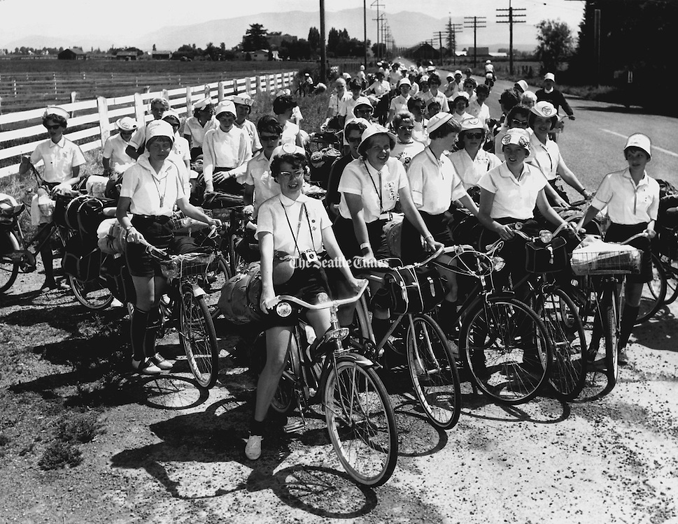 Sixty Girl Scouts and leaders from throughout the Pacific Northwest paused on the second annual San Juan Girl Scout Bike Hike from Mount Vernon. The ten-day ride  finished with a campout at the Blaine Peace Arch Park with Canadian Girl Guides. (Richard S. Heyza / The Seattle Times, 1963)