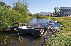 Price Chambers/JACKSON HOLE DAILY.John Ward leaps from the back of his uncle's pickup after his 4-year-old cousin put the truck in gear and rolled into Flat Creek near High School Road on Monday. Some of Ward's family had just finished inner tubing when they borrowed their uncle Arlen's vehicle to transport everything. Elijah Ward, 4, was left in the truck briefly when he pulled the transmission into gear and rolled into the creek on Monday afternoon. No one was injured in the accident.