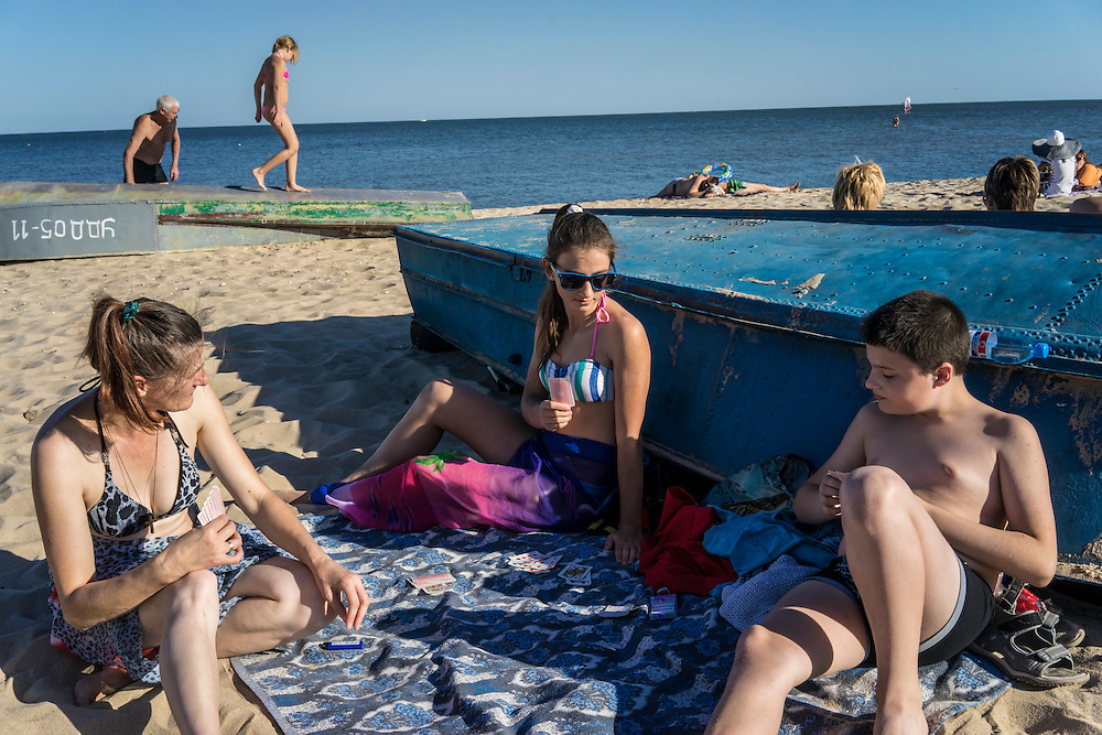 MARIUPOL, UKRAINE - AUGUST 30, 2015: Marina Hamidulina, left, and her son Radion Hamidulin, 11, right, play cards with Yulia Sovyak, 12, a family friend, on Peschanka Beach in Mariupol, Ukraine. The beach is located on the western side of the city, away from the direction of the front lines, though a section has been fenced off and studded with tank traps and concertina wire, while signs warn of land mines. CREDIT: Brendan Hoffman for The New York Times