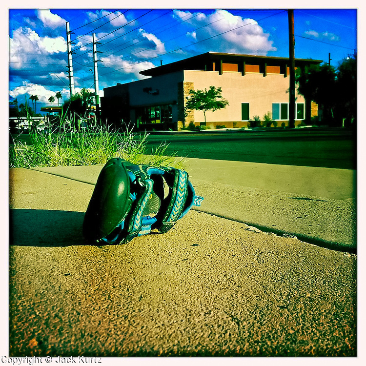 13 NOVEMBER 2011 - PHOENIX, AZ: An infant's sandal on the sidewalk in Phoenix, AZ.  PHOTO BY JACK KURTZ