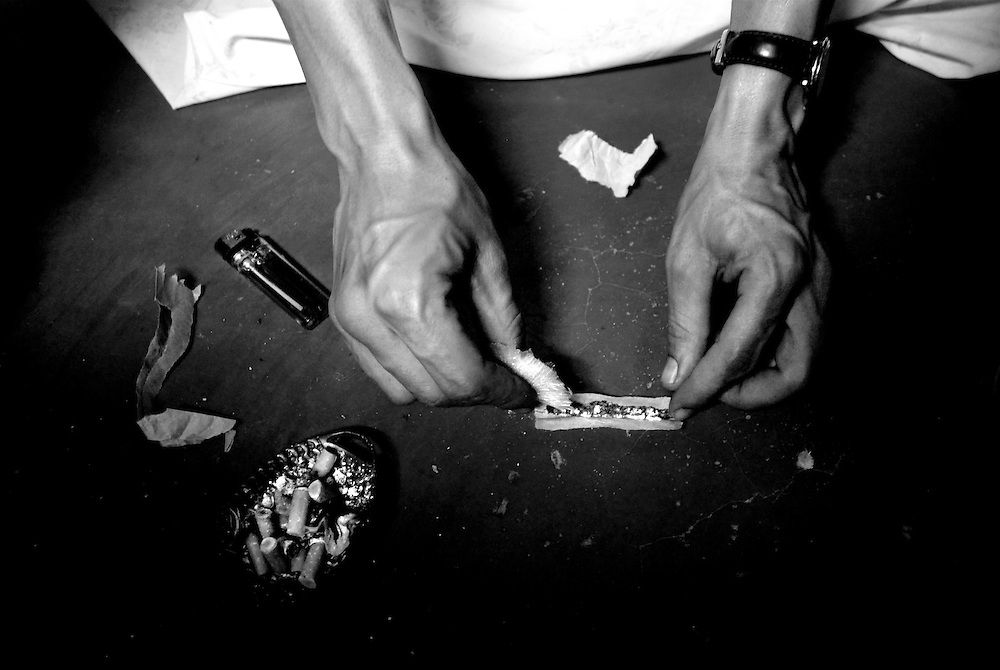 Marco, a heroin addict and street dealer, adds heroin to a marijuana cigarette rolled in paper torn from a bread sack. After completing weeks of blood tests and consultations with psychiatrists for acceptance into a government subsidized drug rehabilitation program, he had even packed his luggage for the six month inpatient program before he changed his mind and decided to stay in his barrio. Marco says he is quitting hard drugs and will only continue to use marijuana and consume alcohol.
