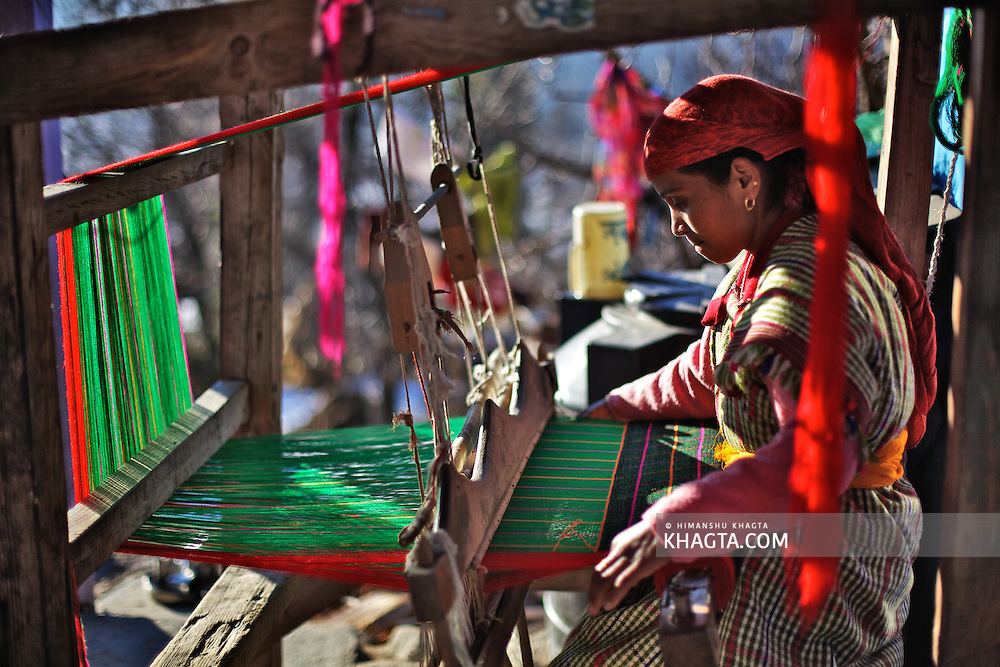 A lady weaving a Kullu Shawl in the backyard of her home in Kullu