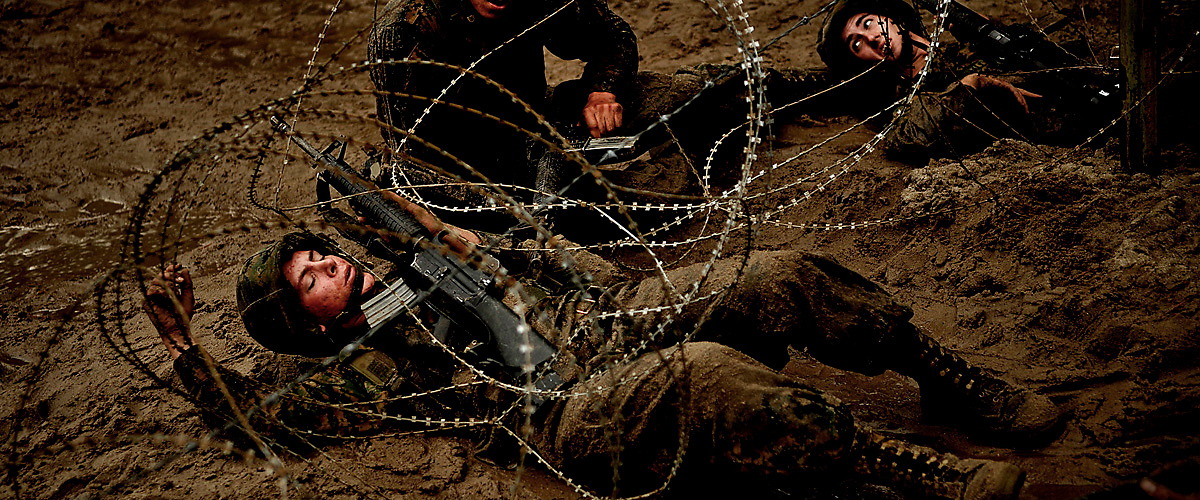 """Exhausted new recruits maneuver under barbwire during a daytime movement simulator training course labeled by the new recruits as the """"Get Back Course"""" (on account of how many times the instructors make them restart the course) on October 15, 2009 at Marine Basic Training in Parris Island, SC. 