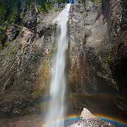 A bright double rainbow forms in the spray at the base of Comet Falls in Mount Rainier National Park, Washington. A 320 feet (98 meters), Comet Falls is one of the tallest waterfalls in the park. Comet Falls was so named because from certain angles, it resembles the head and tail of a comet.