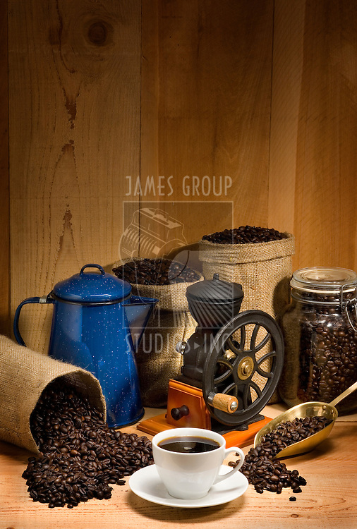 Coffee cup and saucer against a rustic background of burlap bags, coffee beans, coffee grinder, coffee pot and coffee scoop with empty space above for company logo and text