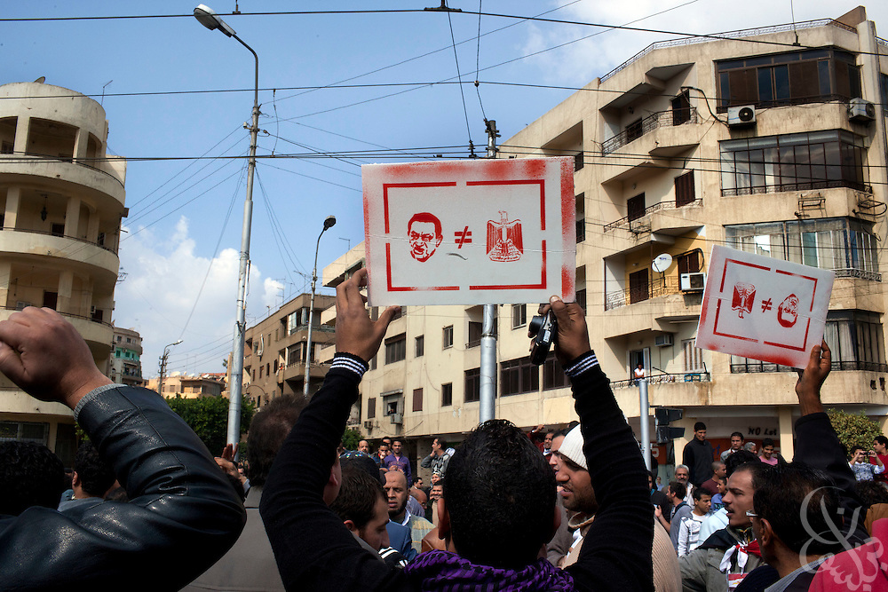 Egyptian anti-government protesters hold anti-Hosni Mubarak signs as they demonstrate outside the heavily guarded Orouba Presidential Palace February 11, 2011 in the Heliopolis district of Cairo, Egypt. Protesters marched Friday on a number of public buildings including the palace in an effort to spread their ongoing protests that are now in their 18th day. (Photo by Scott Nelson)