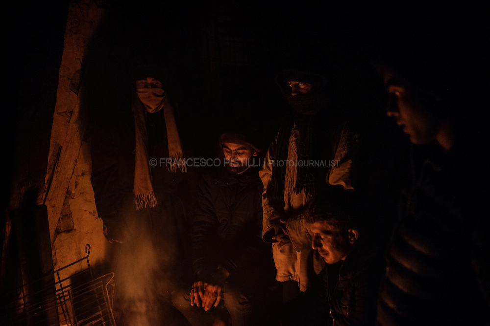 Refugees keep warm near a fire in the abandoned depot behind the central bus station in Belgrade, where they sleep during the night.