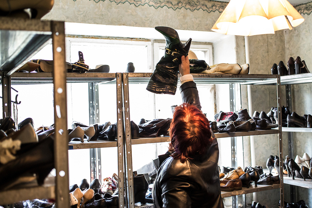 DNIPROPETROVSK, UKRAINE - OCTOBER 10: A woman looks at boots from among a selection of shoes which are available for people who fled with few belongings at The Aid of Dnipro, a charity organization providing assistance to displaced people from Eastern Ukraine, on October 10, 2014 in Dnipropetrovsk, Ukraine. While the charity has received many donations of clothes and toys, they are having a difficult time providing enough food to those in need. The United Nations has registered more than 360,000 people who have been forced to leave their homes due to fighting in the East, though the true number is believed to be much higher. (Photo by Brendan Hoffman/Getty Images) *** Local Caption ***