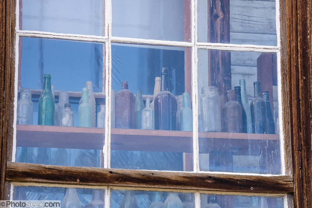 """Glass reflecting blue sky obscures rows of bottles seen behind. Bodie State Historic Park lies in the Bodie Hills east of the Sierra Nevada mountain range in Mono County, near Bridgeport, California, USA. After W. S. Bodey's original gold discovery in 1859, profitable gold ore discoveries in 1876 and 1878 transformed """"Bodie"""" from an isolated mining camp to a Wild West boomtown. By 1879, Bodie had a population of 5000-7000 people with 2000 buildings. At its peak, 65 saloons lined Main Street, which was a mile long. Bodie declined rapidly 1912-1917 and the last mine closed in 1942. Bodie became a National Historic Landmark in 1961 and Bodie State Historic Park in 1962."""