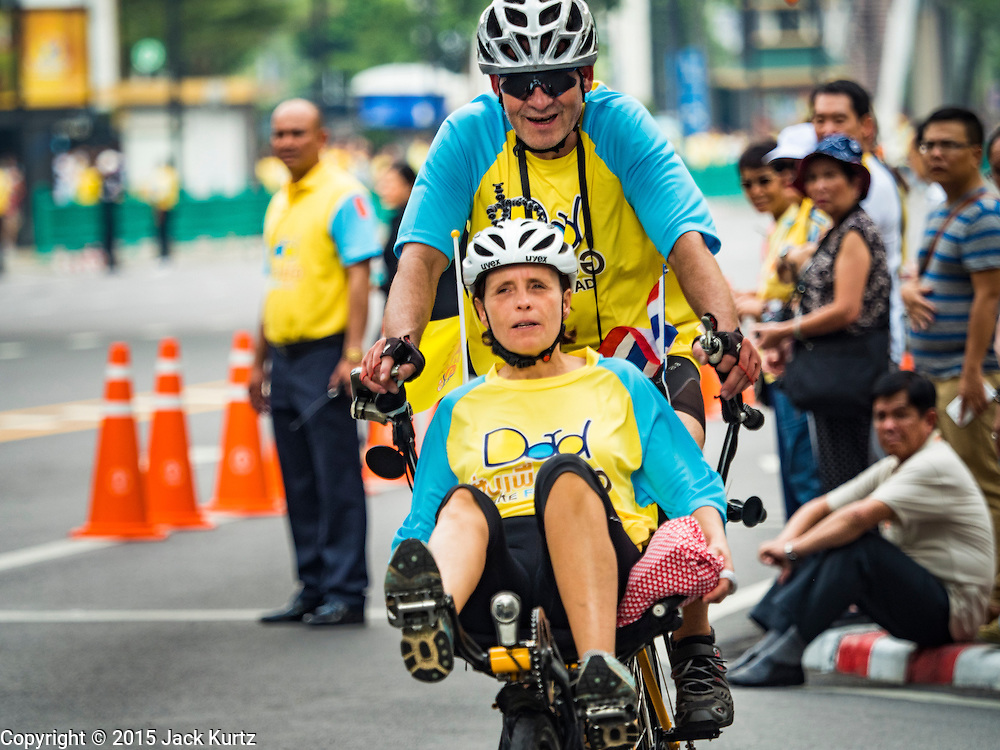 11 DECEMBER 2015 - BANGKOK, THAILAND:  A foreign couple ride their tandem bike during the Bike For Dad in Bangkok. More than 527,000 people registered for the Bike for Dad event to honor Bhumibol Adulyadej, the King of Thailand, whose birthday is also celebrated as Father's Day in Thailand. In Bangkok, 99,999 people registered for Bike for Dad. More than 418,000 people registered for Bike for Dad rides in the provinces outside Bangkok and 9,805 participated in Bike for Dad events outside of Thailand. His Royal Highness Crown Prince Maha Vajiralongkorn, the heir apparent to the Thai crown, led the bike ride in Bangkok. The Bangkok route was 29 kilometers long (18 miles) and traveled through Bangkok and across the Chao Phraya River into Thonburi. Bike for Dad events were held across Thailand.    PHOTO BY JACK KURTZ
