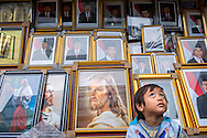 Ilham waits for his family to finish shopping near a stall with framed posters of Jesus, the Qur'an and Indonesian political figures in the Pesar Baru neighborhood, about a mile north of the National Monument, or Monas tower on December 4, 2014 in Jakarta, Indonesia. There are many different religions practiced in Indonesia, though the government officially recognizes Islam, Protestantism, Catholicism, Hinduism, Buddhism and Confucianism. Ann Hermes/© The Christian Science Monitor 2014