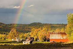 A rainbow over farms in Peacham, Vermont. Fall.
