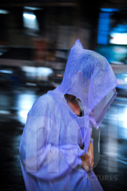 Strange silhouette under a raincoat during monsoon season, Nha Trang, Vietnam, Southeast Asia