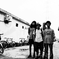 """BEIJING, HAIDIAN DISTRICT,CHINA-AUGUST 15,1999:.a group of punks hang out together in the alley outside the Scream Club before a punk show, August 15, 1999, in China.. In the spring of 1998, a handful of youngsters teamed up to unofficially rebel against conformist Chinese life. They shaved their heads, and founded bands with names like """"Brain Failure"""" and """"Anarchy Boys"""".  To some like Punker Xiao Rong, this lifestyle was an extension of the life he'd begun as a school dropout at age sixteen.-Although the majority of the punks came from well-off families, they preferred to live in self-imposed poverty. .The Scream Bar and its surrounding dusty alleyways in the student district became the center of youthful rebellion until it was closed . The punks bands have moved on to other bars in Beijing, some got contracts with foreign record companies and even toured Europe, Japan and the"""