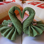 Two green towels are folded like snuggling swans in a private double room at Berggasthaus Meglisalp, which can only be reached on foot in the spectacular heart of the Alpstein mountain chain in the Appenzell Alps, Switzerland, Europe. This authentic mountain hostelry, owned by the same family for five generations, dates from 1897. Meglisalp is a working dairy farm, restaurant and guest house surrounded by majestic peaks above green pastures.