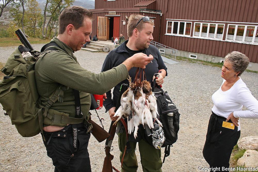 Det har vært folksomt på Nedalshytta i hele sommer. Torkel Eng t.v. og Kristian Lillehagen fra kongsvingen har leid seg full pakke med rypejakt og er meget fornøyd med terrenget og fangsten. Som her blir vist fram til vertinne Svava Opheim fra Stjørdal. Foto: Bente Haarstad Nedalshytta eies og drives av Trondhjem Turistforening, og er en av de tre betjente DNT-hytterne i Sylene. Mountain cabin owned by the norwegian hiking organization.