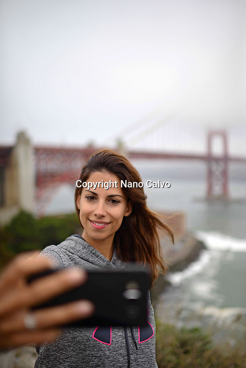 Young woman takes a selfie with Golden Gate Bridge, San Francisco.
