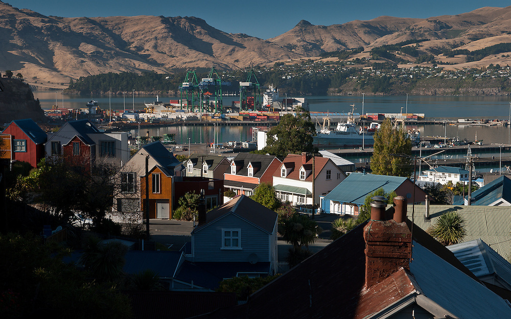 Clear weather view over Lyttelton rooftops to the port, cargo terminal and Banks Peninsula mountains beyond