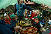 Svizzera, San Gallo, asilo nel bosco , un piccolo casottino in legno è il rifugio in caso di forte pioggia...le lezioni solitamente si volgono sempre all'aperto per tutto l'inverno  . children are even involved in cooking the lunch...lunch in the tent....Switzerland, St. Gallen, kindergarten in the wood. Children are free to run and enjoy in the wood no matter cold or snow...playing after lunch in the tent...