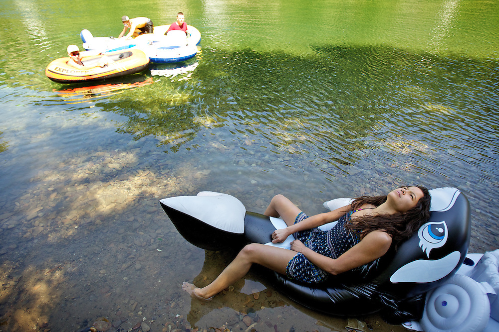 Carly Garcia, 17, waits for her inflatable orca to deflate after finishing her float Wednesday down the Coeur d'Alene River.