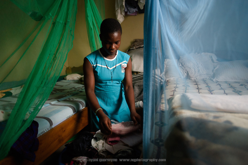 "Peninah Mamayi, the Health Prefect at Achilet Primary School near Tororo in Eastern Uganda, folding away laundry at home on 1 August 2014. As Health Prefect she educates her peers on a range of health and hygiene issues, including menstrual hygiene. She says, ""I wanted to be a health prefect so I could help my friends be clean. I teach them about cleaning their latrines at home, keeping their compounds clean at home, cutting their hair and fingernails, washing their clothes. I tell them that after they pick rubbish they should wash their hands. I tell them to be bathing daily so that they don't smell. And to wash their Afripads very well, and to dry them very well."" An Afripads customer herself, she says Afripads (locally manufactured reusable sanitary pads) ""have improved my life because they don't disturb me, and I can just sit and be comfortable. Even if I play or I jump, nothing happens."""