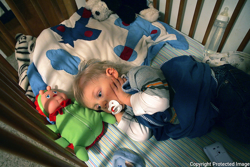 After playing with his toys, the energetic Drake Weland crawled into his bed for quick nap.  Weland, who was born deaf, hears with the aid of cochlear implants.  He removed them himself before lying down.
