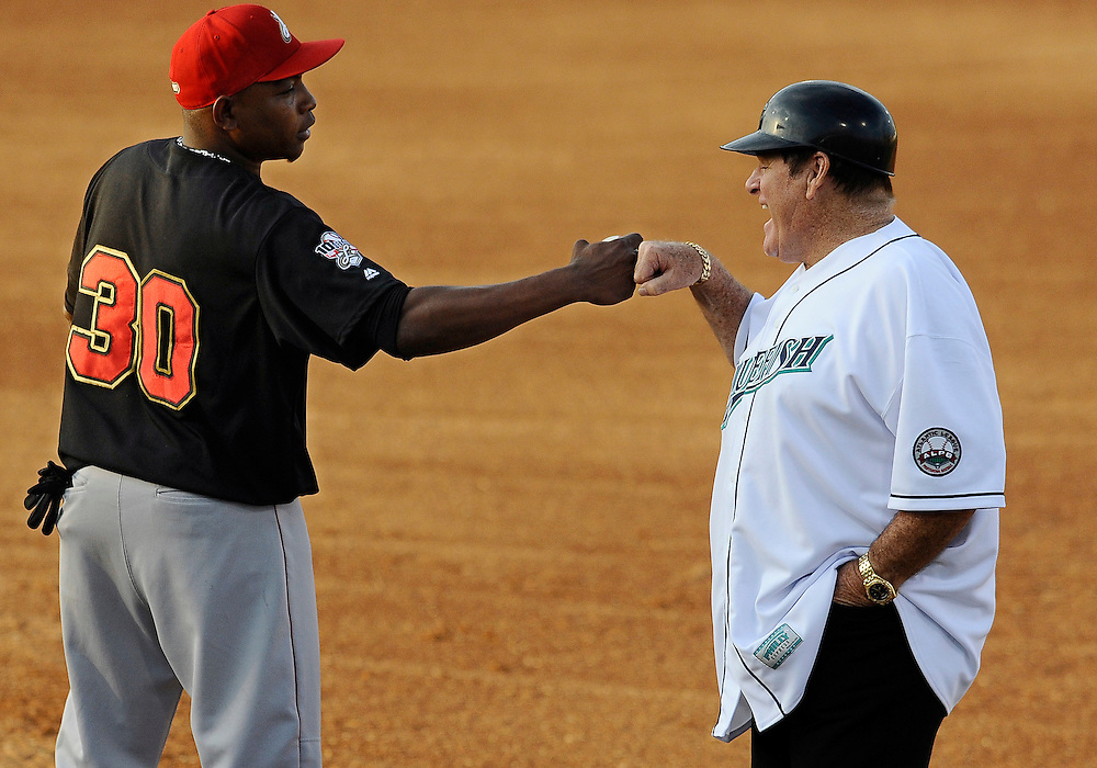 Pete Rose, right, fist bumps with Lancaster Barnstormers' Wilson Batista, Monday, June 16, 2014, in Bridgeport, Conn. Rose, banned from Major League Baseball, returned to the dugout for one day to manage the independent minor-league Bridgeport Bluefish. (AP Photo/Jessica Hill)