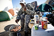 RENO, NV - OCTOBER 6:  A homeless man cooks breakfast in a tent city for the homeless in downtown Reno, Nevada October 6, 2008. The City of Reno set up the tent city when existing shelters became overcrowded as Nevada struggles with one of the highest unemployment rates in the country. (Photo by Max Whittaker/Getty Images)