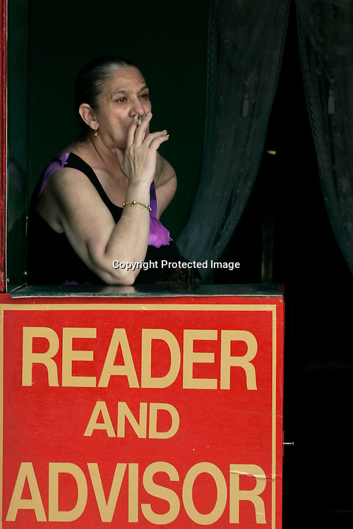 A fortune teller works at the Astroland Amusement Park in New York, May 27, 2007. The Coney Island amusement closes for goods at the end of the 2007 season ahead of a major redevelopment that will raze much of the lovably seedy boardwalk area. REUTERS/Keith Bedford (UNITED STATES)