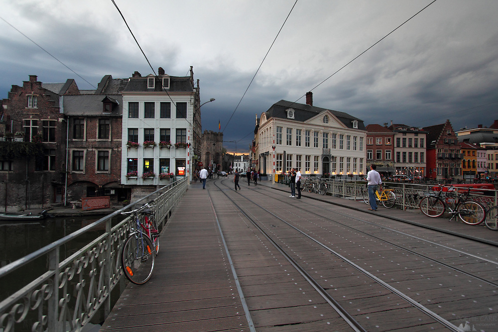 Tramlines across a bridge over the River Leie in Ghent old town, Belgium with dark storm clouds in the distance