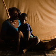 Inoussa Ouedraogo (4) and his mother, Minata Ouedraogo (38), under the mosquito net they share at their home in the village of Songodin in the Sanmatenga region of Burkina Faso on 25 February 2014. Mosquito nets greatly decrease the incidence of malaria by reducing the risk of being bitten by the nocturnal Anopheles mosquito, which carries the malaria parasite.