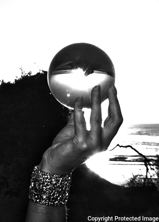 Black and white image of woman's hand holding crystal ball on Jekyll Island Beach