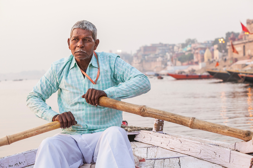 A Indian man rowing a boat for tours on the Ganges river, Varanasi, India.