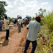 A Plan International driver pulling a winch towards a tree while trying to free his stuck vehicle along a road just outside of Juba, the capital of South Sudan on 7 August 2014. Two trucks had become stuck, one of which remained there for at least five days despite effots to free it. During the rainy season, road travel in South Sudan becomes extremely challenging; some parts of the country become completely inaccessible.