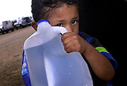 A child illegal immigrant from Mexico, traveling with about 75 others, peeks out from behind a water bottle near Sells, Arizona on the Tohono O'odham Nation.