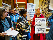 """04 MAY 2017 - ST. PAUL, MN: People protesting in favor of paid sick leave and a higher minimum wage walk past a woman dressed as a handmaid (from the novel and Hulu series """"A Handmaid's Tale"""") at the Minnesota State Capitol. About 50 people came to a protest to urge Minnesota State Senators to vote against two bills supported by the Republican party that would restrict access to women's health care in Minnesota. The protest was organized by  NARAL Pro-Choice Minnesota, NCJW Minnesota, and Planned Parenthood Minnesota. The Senate passed the bills but Minnesota's Democratic governor is expected to veto the legislation when it reaches his desk.     PHOTO BY JACK KURTZ"""