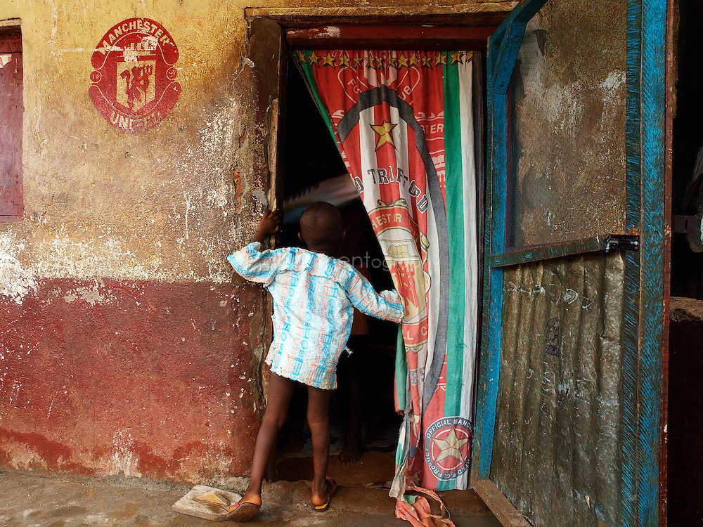 A boy enters the house of a Manchester United fan, Kroo Bay, Freetown, Sierra Leone