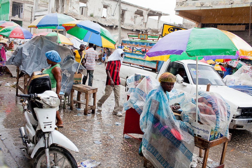 A brief rainshower hardly phases pedestrians and vendors along Grand Rue on July 7, 2010 in Port-au-Prince, Haiti.